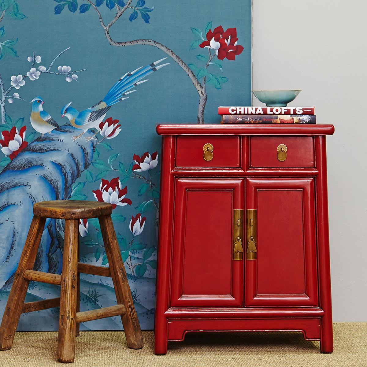 A wooden stool and red cabinet set against lovely blue wallpaper