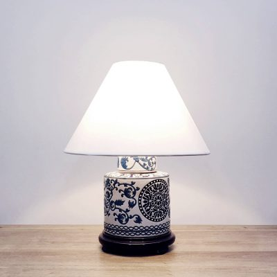 A round porcelain table lamp with blue & navy patterns and a wooden base