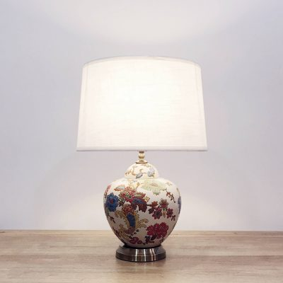 A round ceramic table lamp with a cream base with colourful floral designs and a metallic base