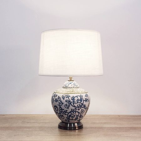 A round ceramic table lamp with a white base with blue and green floral lines and a metallic base