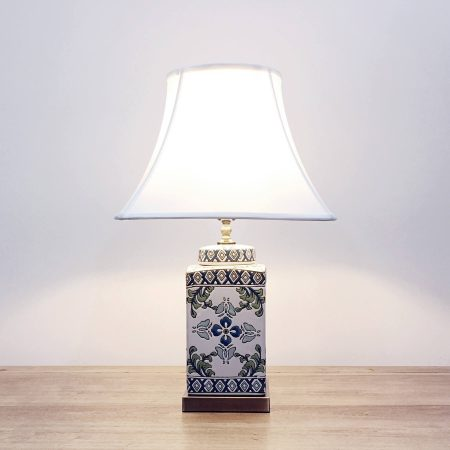 A square ceramic table lamp with a white base with green & blue floral designs and a metallic base