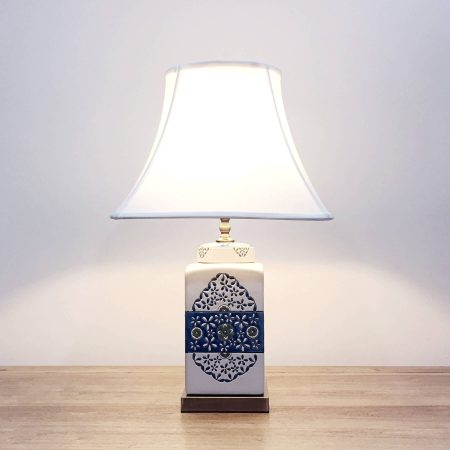 A square ceramic table lamp with a white base with green & blue floral motifs and a metallic base