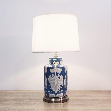 """A round ceramic table lamp with a blue base and """"ikat"""" design and a metallic base."""