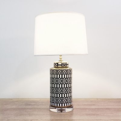A cylindrical ceramic table lamp with black & white geometric patterns and an acrylic base.