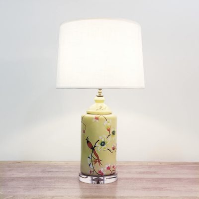 A round ceramic table lamp with a yellow base with birds & flowers motifs and an acrylic base