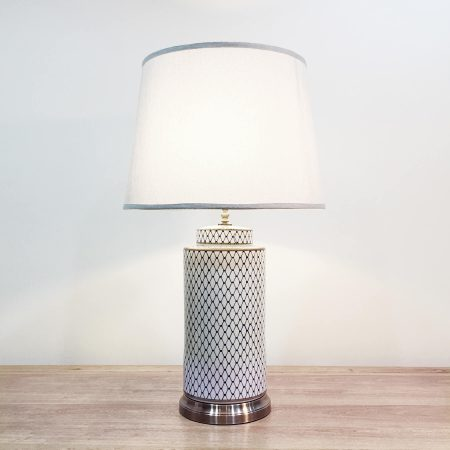 A tall round ceramic blue & white table lamp with a metallic base