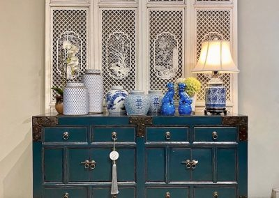 Teal sideboard with metal details and a set of carved white wooden screens